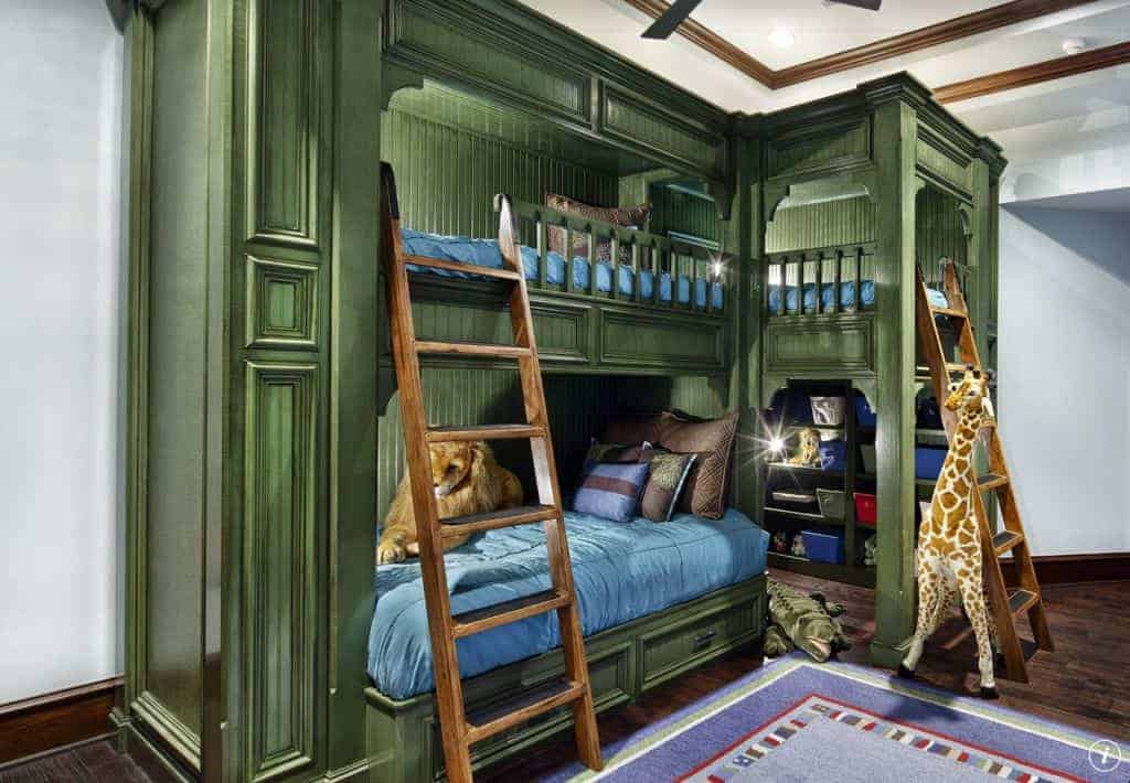 Kids bedroom with a jungle theme boasting a blue bordered rug and moss green beadboard bunk bed integrated with open shelving underneath.