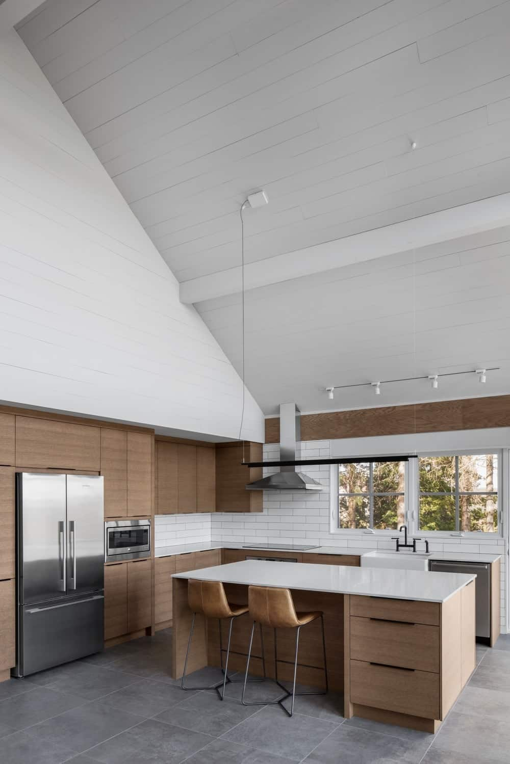 The modern three-door fridge and oven are both embedded into the large wooden structure connected to the L-shaped peninsula that has a white countertop that emphasizes the stainless steel dishwasher beside the sink area.