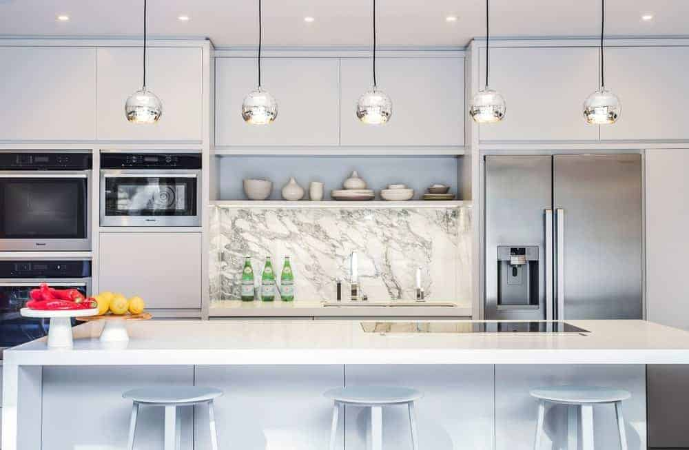 This is a lovely kitchen that emphasizes the stainless steel fridge and the rest of the appliances. This is achieved by the uniformity of the white hues in the white ceiling, white marble backsplash and the white countertops.