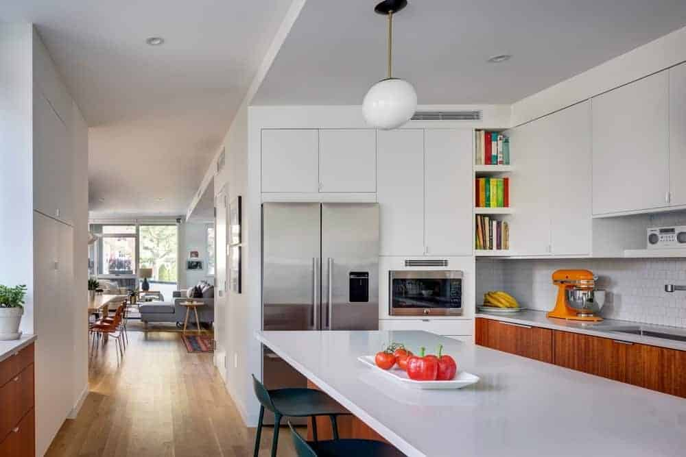 The stainless steel fridge and oven are embedded into the white wooden structure that blends with the white ceiling and hanging cabinets above the white countertop of the peninsula contrasted by the wooden cabinets and flooring.