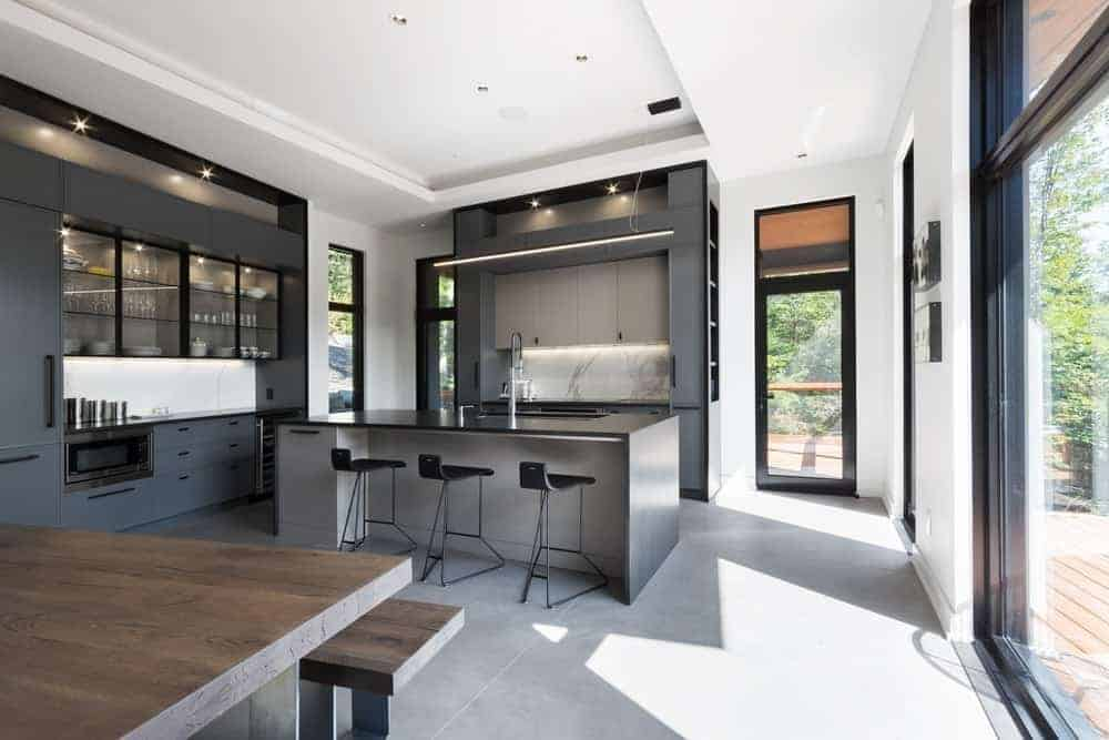 The brilliant white tray ceiling contrasts the dark gray structures of the kitchen peninsulas and island that has black countertops that matches the handles of the cabinets and drawers housing the modern appliances.