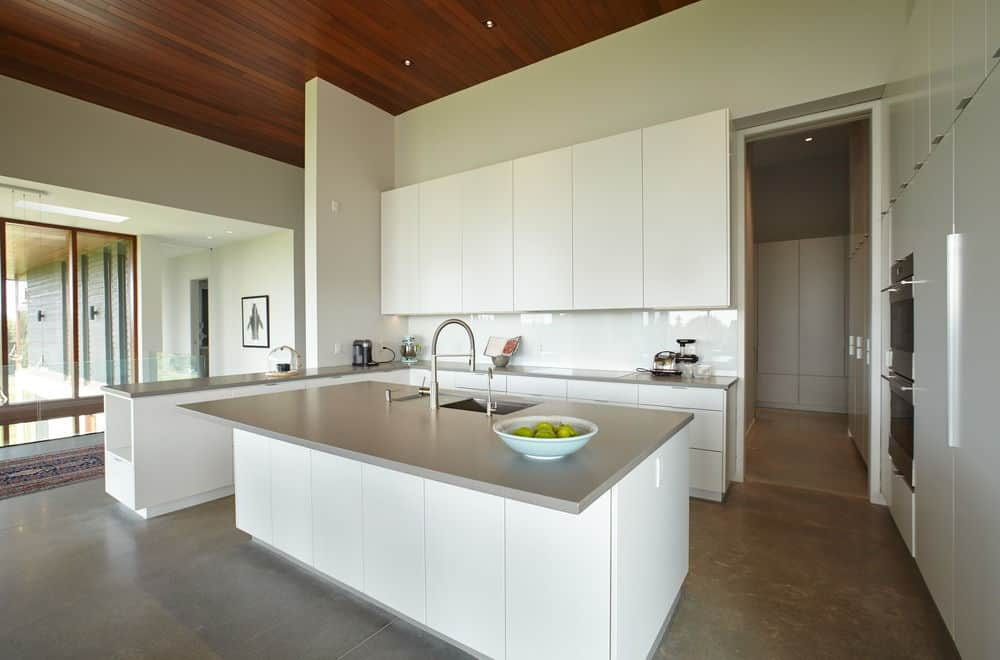 This lovely kitchen is predominantly white that makes the gray surfaces of the countertops and flooring stand out. Among these stand-outs, are the stainless steel appliances and fixtures that solidify the modernistic theme of the kitchen.