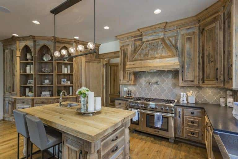 This charming and cozy kitchen has a bare wooden palette applied on its kitchen island surrounded by cabinets and an L-shaped peninsula with the same hue but is given a black countertop. This rustic quality is contrasted by the modern stove-top oven that has an elegant patterned gray backsplash.