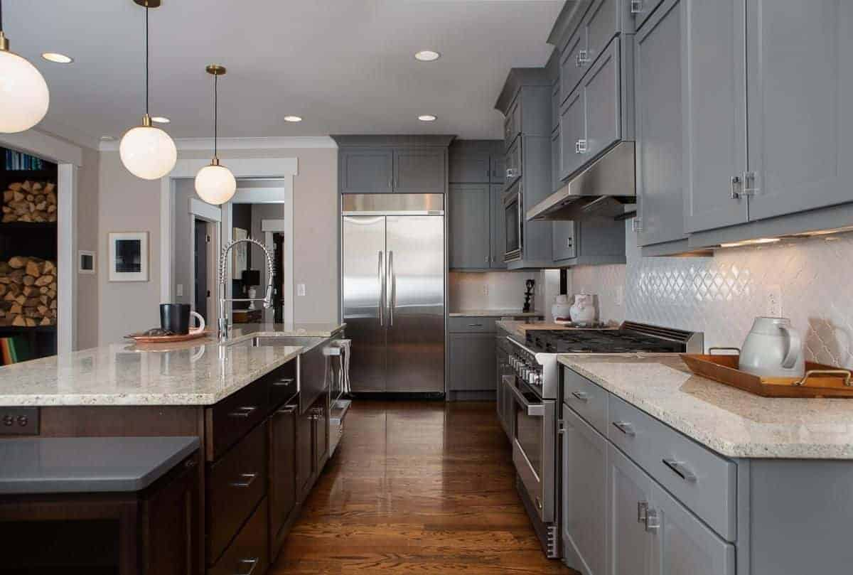 This kitchen has a long peninsula paired with a large gray kitchen island forming a small hallway of dark hardwood flooring leading to a far wall dominated by a white structure housing the modern appliances.