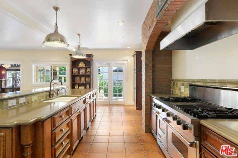 The terracotta flooring tiles is matched with redwood shaker cabinets and drawers for that classic theme paired with moss green countertops and backsplash that makes the stainless steel stove stand out as well as its vent hood against the red brick alcove.