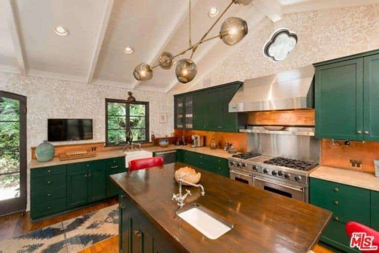 The green shaker cabinets and drawers dominate the kitchen and makes the stainless steel stove-top oven stand out along with its vent hood. These elements are mediated by the terracotta backsplash and white cathedral ceiling.