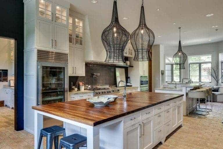 The stand-out elements of this lovely kitchen are the three pendant lights that have rustic black woven hoods hanging from the white ceiling that blends with the white cabinets flanking the white vent hood of the stainless steel stove oven.