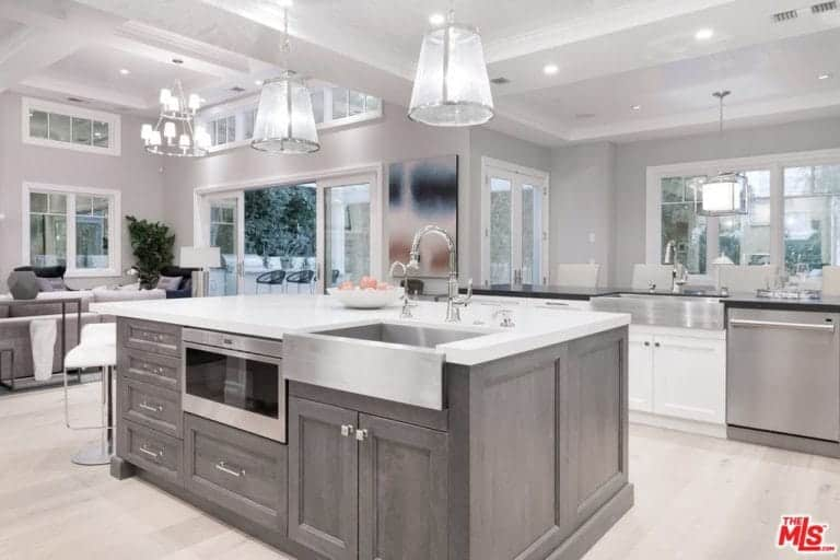 This is a bright kitchen due to its high white coffered ceiling paired with a light hardwood flooring and white pendant lights that brighten up the white countertop and gives a sheen to the stainless steel appliances against the gray cabinets.