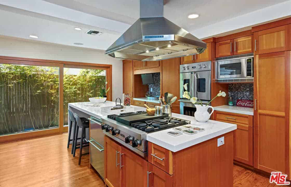 The large stainless steel vent hood hangs from the middle of the white tray ceiling over the stainless steel stove housed in the redwood kitchen island that has the same white countertop as the peninsula.