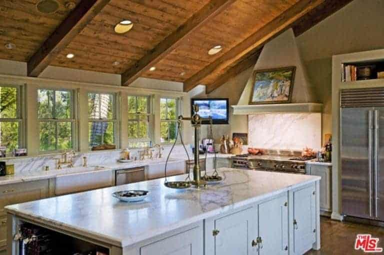 This lovely kitchen has a wooden cathedral ceiling that has exposed beams and recessed lights that augment the natural light coming in from the row of windows above the white marble backsplash of the L-shaped peninsula that houses the stainless steel appliances.