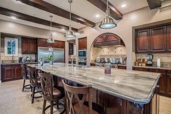 This kitchen has a brilliant ceiling contrasted by its dark wooden exposed beams and the three stainless steel pendant lights hanging over the large kitchen island. These pendant lights pair well with the modern stainless steel appliances that stand out against the dark wooden cabinets.