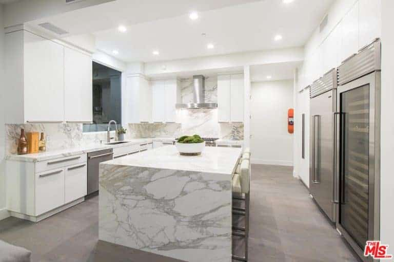 The white marble waterfall kitchen island matches with the countertop and backsplash of the L-shaped peninsula that houses the stainless steel dishwasher matching with the modern fridge on the other side of this lovely kitchen.