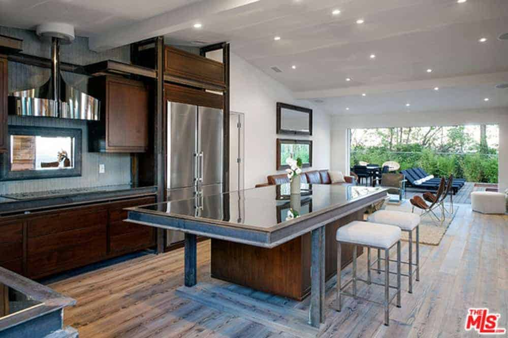 The kitchen island has a sleek countertop that matches with the stainless steel fridge and the modern vent hood over the cooking area. This is contrasted by the dark wooden cabinets and drawers that also contrasts the white cathedral ceiling.