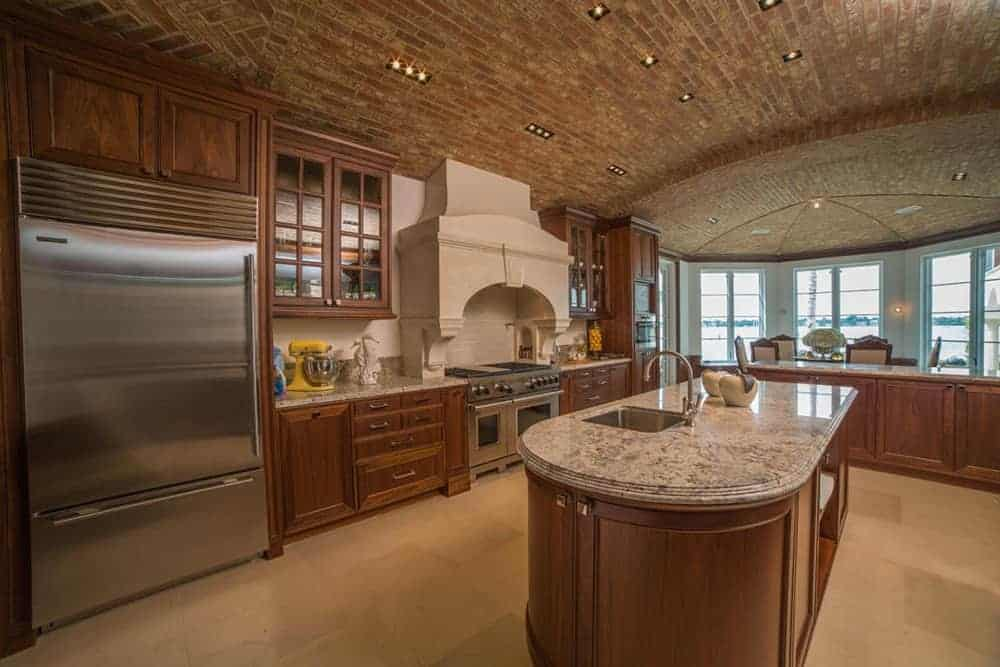 The large two-door stainless steel fridge is built into the wooden structure that is connected to the peninsula that has cabinets and drawers flanking the stainless steel stove-top oven with a beige stone chimney contrasting the brick stone cove ceiling.