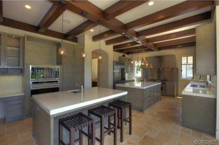 This kitchen has large wooden exposed beams on its ceiling. These beams support three pendant lights that cast off a warm yellow light on the two kitchen islands and the stainless steel appliances built into the walls flanking the arched entryway.