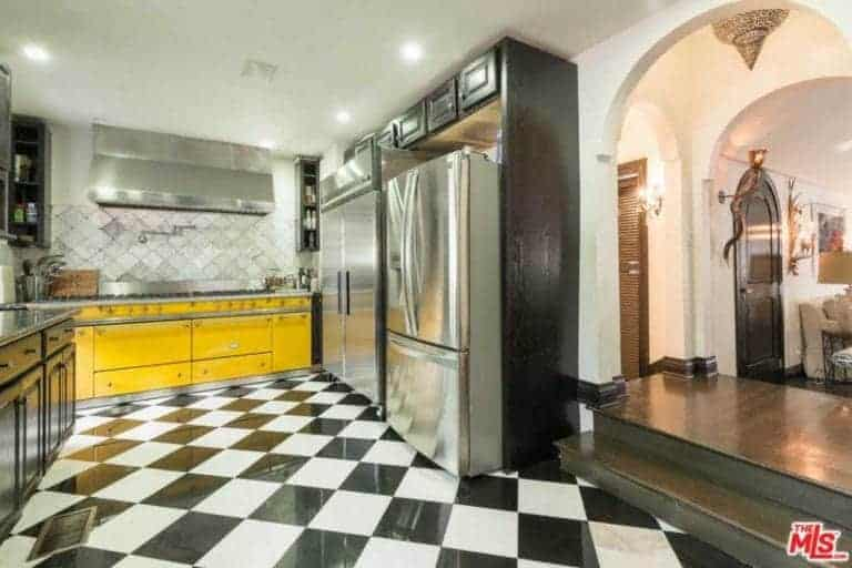 The black and white checkered flooring is the highlight of this charming kitchen that complements the stainless steel appliances dominating the kitchen peninsula. The yellow facade of the large oven stands out against the black and stainless steel hues flanking it.