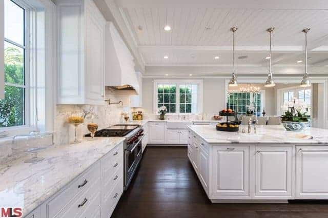 This bright and spacious kitchen is augmented by the white L-shaped peninsula and white ceiling with three stainless steel pendant lights over the white kitchen island. This matches well with the stainless steel stove-top oven paired with a white vent hood.