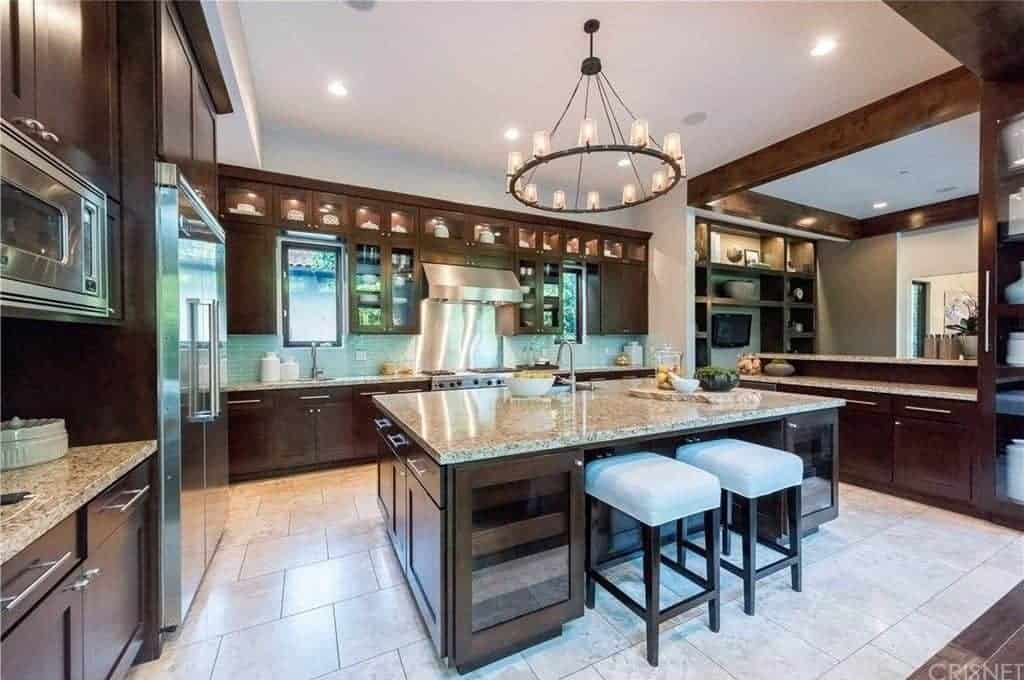 This charming kitchen is dominated by the dark wood elements on the kitchen island, peninsulas and the mounted cabinets matching the farmhouse chandelier. This is contrasted by the beige countertops and the stainless steel appliances.