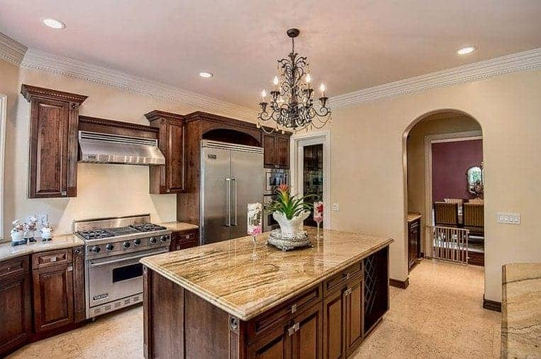 The beige ceiling bears recessed lights and an intricate wrought iron chandelier in the middle that gives a sheen on the stainless steel fridge and stove-top oven that has a modern vent hood floating above it flanked by wooden cabinets.
