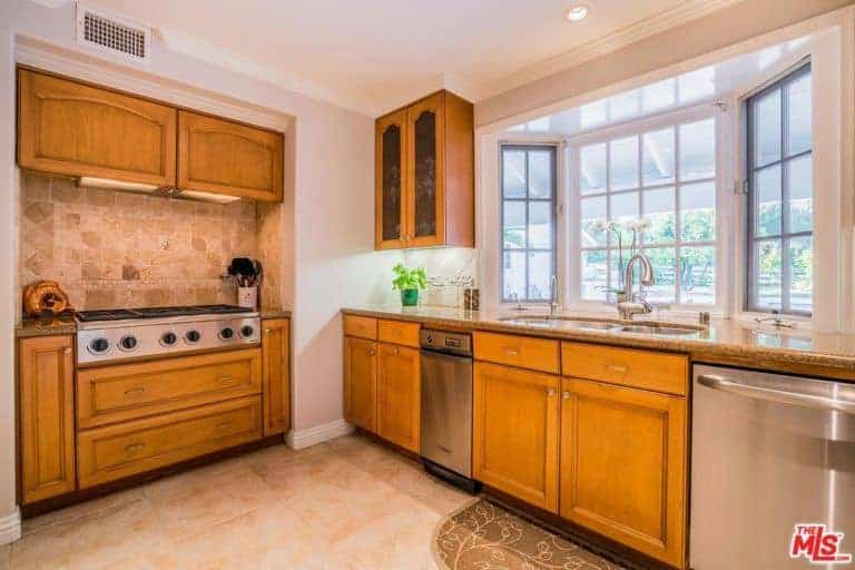 This simple and homey kitchen has two kitchen peninsulas. One side houses the stainless steel stove-top oven in wood while the adjacent one has the dishwasher beside the dual-basin sink area that has an alcove of windows.
