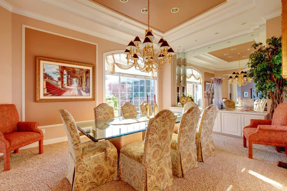 Large dining room featuring carpet flooring and beige walls. It has a glass top dining table along with classy seats, lighted by a gorgeous chandelier hanging from the tray ceiling.