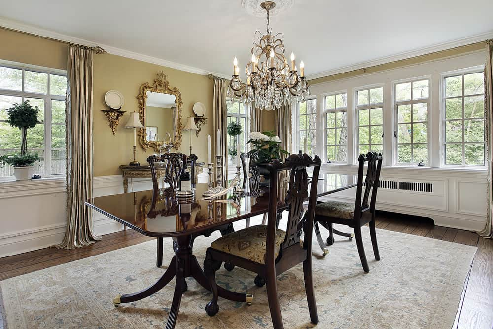 Large dining room featuring an elegant dining table and chairs set on top of a large area rug covering the hardwood flooring. The table set is lighted by a glamorous chandelier.