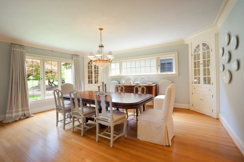 A spacious dining room featuring blueish gray walls and hardwood floors. The room offers a large dining table set lighted by a gorgeous chandelier.