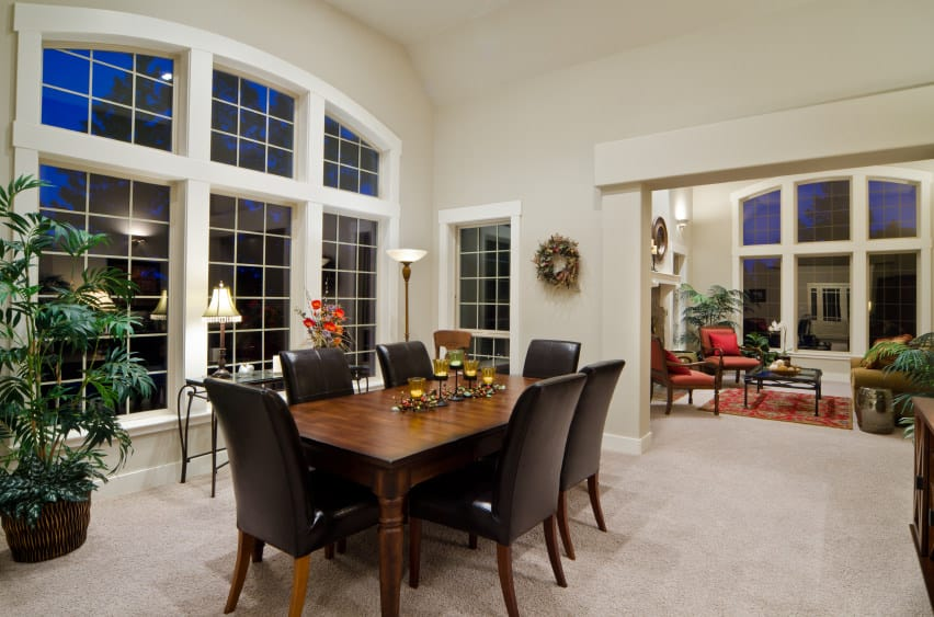 Large dining room with a tall ceiling and carpeted flooring. The room offers a wooden dining table set with black seats.