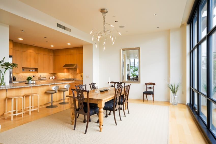A dine-in kitchen featuring a wooden dining table along with classy seats, lighted by a fancy ceiling light. The kitchen also offers a breakfast bar island.