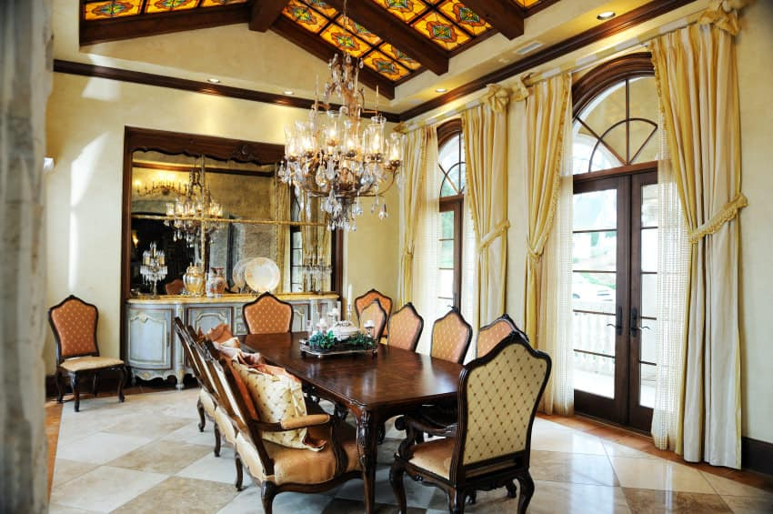 Large dining room boasting a tall vaulted decorated ceiling with exposed beams, along with checkered flooring. It offers a beautiful dining table and chairs set lighted by a glamorous chandelier.
