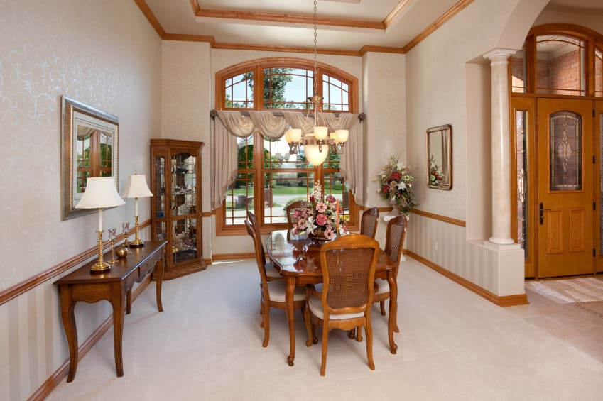 A classy dining room featuring carpeted flooring and a tall tray ceiling. The room offers a wooden dining table set along with a corner cabinetry and a side table.
