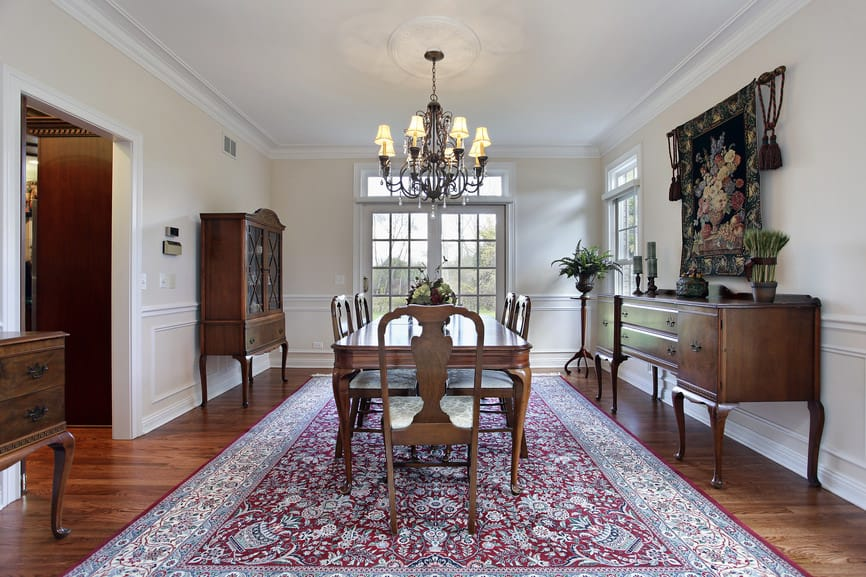 Large dining room featuring a large area rug covering the hardwood flooring. The dining table and chairs set is lighted by a fancy chandelier.