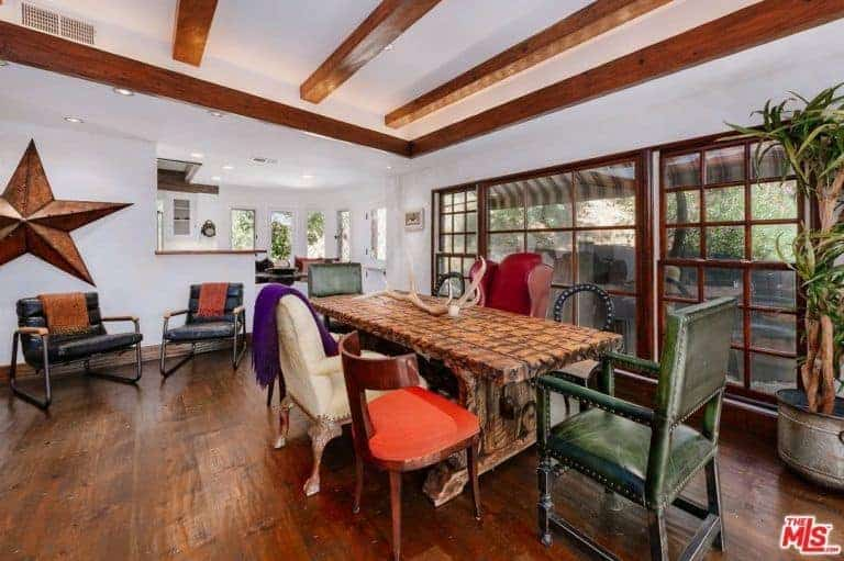 Spacious dining room with hardwood floors, white walls and a white ceiling with beams. The room offers a stylish dining table with colorful seats.