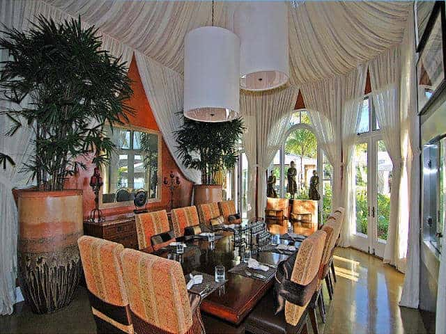 Large dining room featuring a tall and stunning ceiling. It offers a rectangular dining table set with 10 seats and is lighted by large pendant lights.