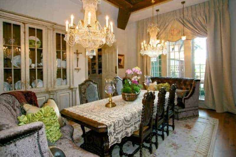A dining room boasting elegant table and chairs set, lighted by two glamorous chandeliers hanging from the home's tall ceiling with exposed beams.