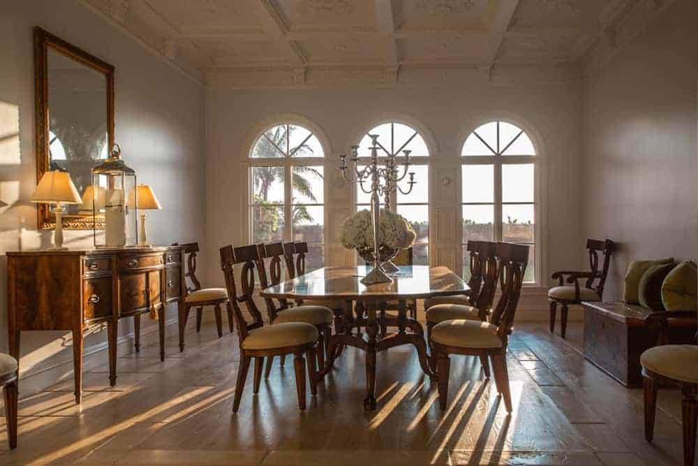 Large dining room featuring a tall coffered ceiling. The room has a large rectangular thin top dining table set with classy chairs.