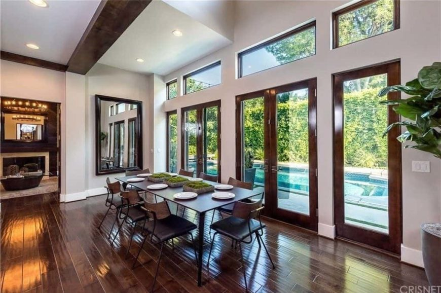 A spacious dining room featuring hardwood flooring and doorways leading to the outdoor area with a swimming pool. The dining room has a dining table and chairs set for eight.