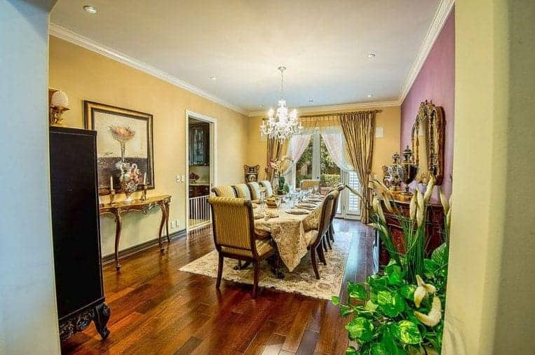 Large dining room featuring an elegant dining table and chairs set lighted by a gorgeous chandelier. The dining table is surrounded by yellow walls and hardwood floors.
