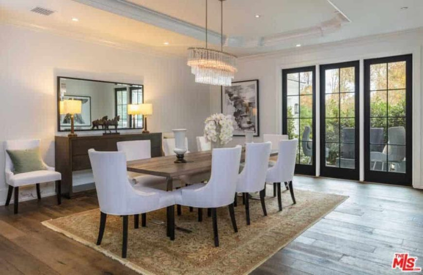 Large dining room featuring a gorgeous ceiling and hardwood flooring topped by a classy area rug where the dining table and chairs are set. The dining area is lighted by beautiful ceiling lights.