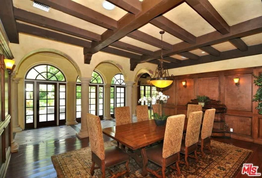 Large Mediterranean dining room featuring hardwood flooring and a ceiling with exposed beams. The room features a wooden dining table with a set of elegant seats, lighted by a pendant light.