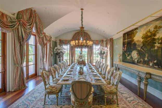 Large dining room with a long dining table set paired with elegant seats on top of a large area rug covering the hardwood flooring. The large wall decor is absolutely stunning. The area is lighted by a glamorous chandelier.