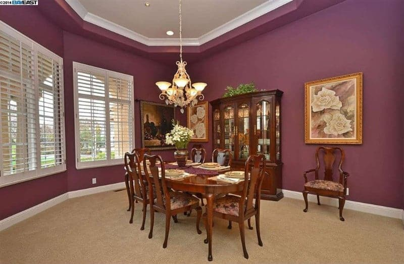 Large dining room featuring a wooden oval dining table set with matching wooden seats lighted by a gorgeous ceiling light. The room has carpeted flooring and is surrounded by purple walls.