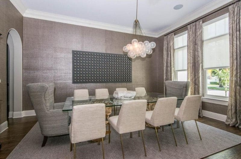 Large dining room with gray walls and hardwood flooring. The room offers a glass top dining table with a set of modish seats on top of a large gray area rug.