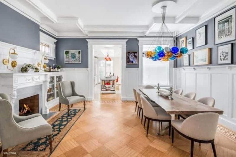Large dining room with stylish hardwood flooring and a well-designed ceiling. The room offers a rectangular wooden dining table set lighted by colorful ceiling lights along with a fireplace on the side.