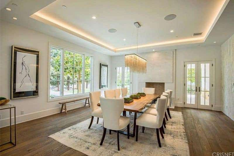 Spacious dining room featuring hardwood flooring and a tray ceiling. The room offers a long dining table set with white chairs on top of a large area rug, lighted by beautiful ceiling lights.