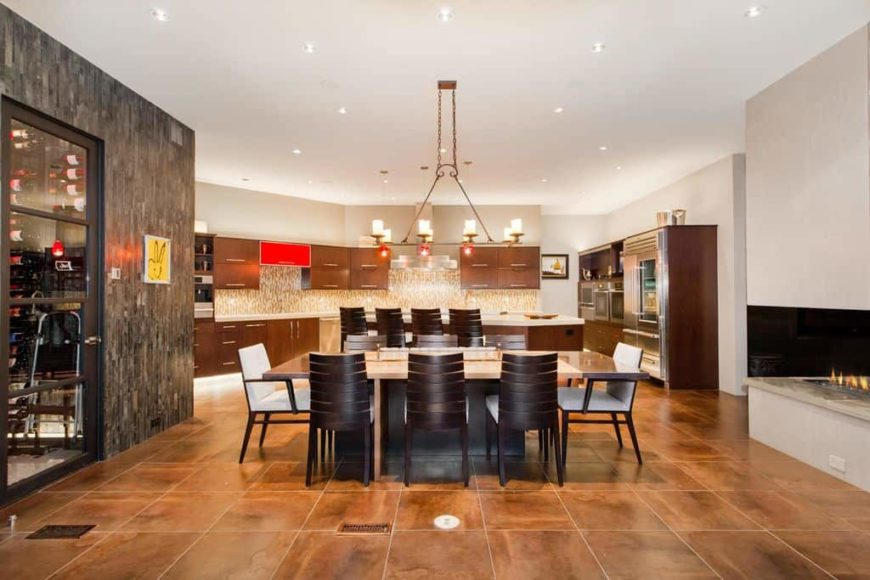 A very spacious dine-in kitchen with brown tiles flooring. It features a large rectangular dining table set lighted by scattered recessed ceiling lights.