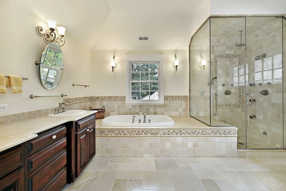 A spacious primary bathroom with a drop-in tub on a tiles platform along with a walk-in shower area. The room is lighted by classy wall lights.