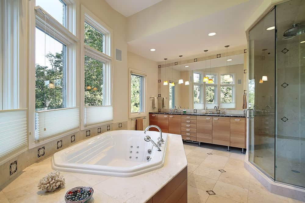 Primary bathroom with a tall ceiling and classy tiles flooring. It offers a drop-in tub and a sink counter with two sinks, along with a walk-in shower room.