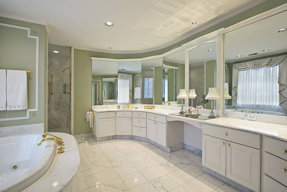 Large primary bathroom with marble tiles flooring and green walls. It has a classy drop-in soaking tub and sink counters with a powder desk in the middle. There's also a walk-in corner shower.