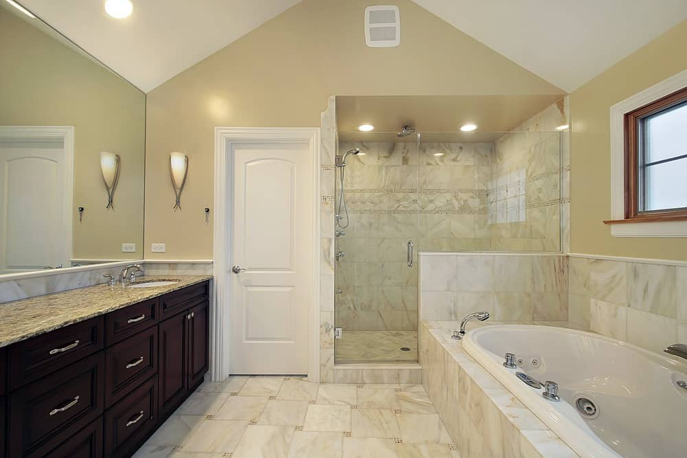 Large primary bathroom featuring a long granite sink counter, a drop-in soaking tub and a walk-in shower room. The room also features a vaulted ceiling.